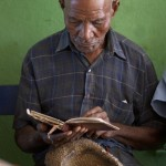 Aleman Joseph reads his Bible while waiting to be treated at a mobile medical clinic set up in the nursing home in Monte Christy, Dominican Republic.