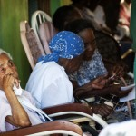 America Pimentel sits in her rocking chair as other women chat beside her in the nursing home Casa de Ancianos Bettel in Monte Christy, Dominican Republic.  Even in the nursing home, Dominicans and Haitians feel resentment toward one another from the countries' heated histories.