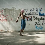 A young boy plays soccer on the streets of Port-au-Prince on January 9, 2011.  Life continues even as the country struggles to rebuild after a devastating earthquake on January 12, 2010.