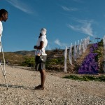 "Duverna Joseph, 37, stands with a friend in front of a memorial at the mass grave of those who died during Haiti's earthquake. ""I lost my leg exactly one year ago today,"" said Duverna. ""So I came to remember those who died and to thank God for being alive."""