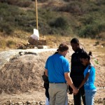 Missionary John Fitts prays with the Gilles family at the mass grave on January 12, 2011.