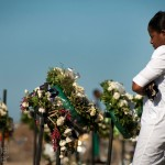 Celine Pierre looks at crosses adorning the mass grave while remembering loved ones who died on January 12, 2011.