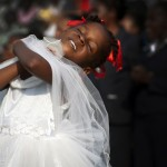 A young girl dances as Haitians sing praise music at the Festival of Hope hosted by Samaritan's Purse to memorialize the one-year anniversary and to hear Franklin Graham speak about hope in Christ.