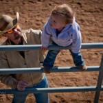Shane Henderson protects his two-year old daugther from falling from the fence at the Sierra Vista Riding Club during Family Ranch Sunday hosted by the cowboy church on January 8, 2012.