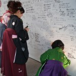 Graduates on the way to a party stop to sign their name on a wall showing their support for Japan on March 11, 2012.
