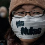 A young anti-nuclear protester turns her surgical mask into a protest sign while walking through Tokyo, Japan, on March 11, 2012.