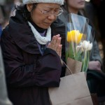 A Japanese woman prays for last year's tsunami victims during a moment of silence commemorating the event at 2:46 p.m., the time the quake struck, in Hibiya Park downtown Tokyo, Japan.