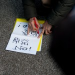 A protester creates a sign to carry while demonstrating against nuclear energy on March 11, 2012.